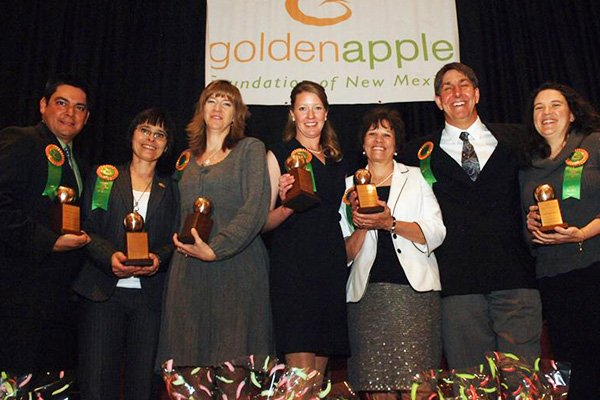 Teachers Holding Golden Apple Trophies Smiling In A Row