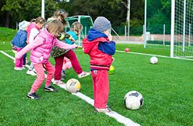 Elementary Kids Playing Soccer In Coats Outside