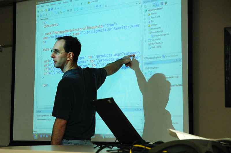 Man Pointing At Large Projector Screen With Computer Code