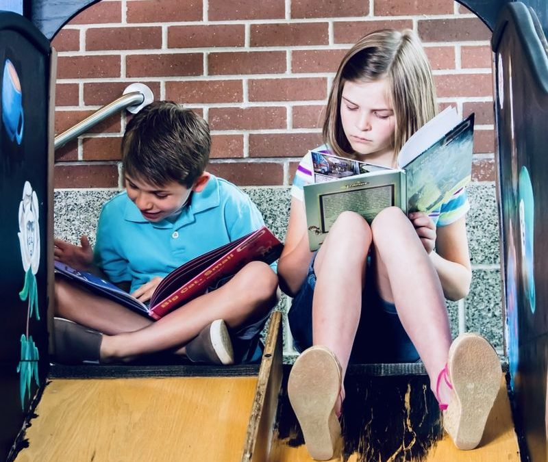Boy and girl sitting next to each other reading books.