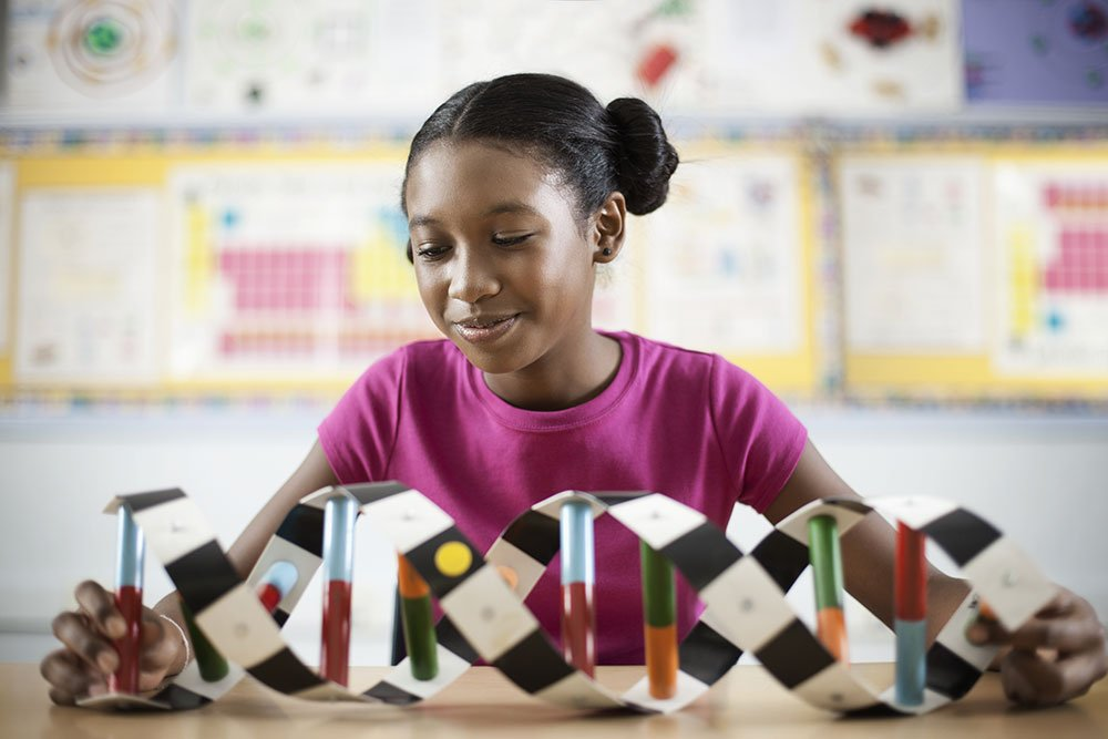 Girl In Science Class Smiling At A Model Of A Helix She Made