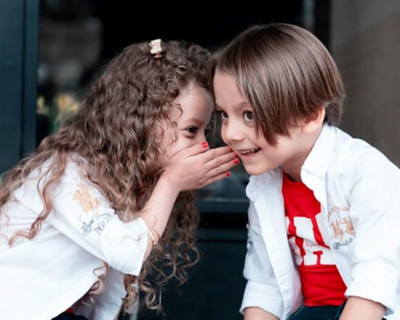 Children smiling and sharing a happy secret
